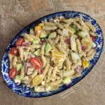 Easy Greek Pasta Salad in an oval, bright blue, ornamental serving bowl.