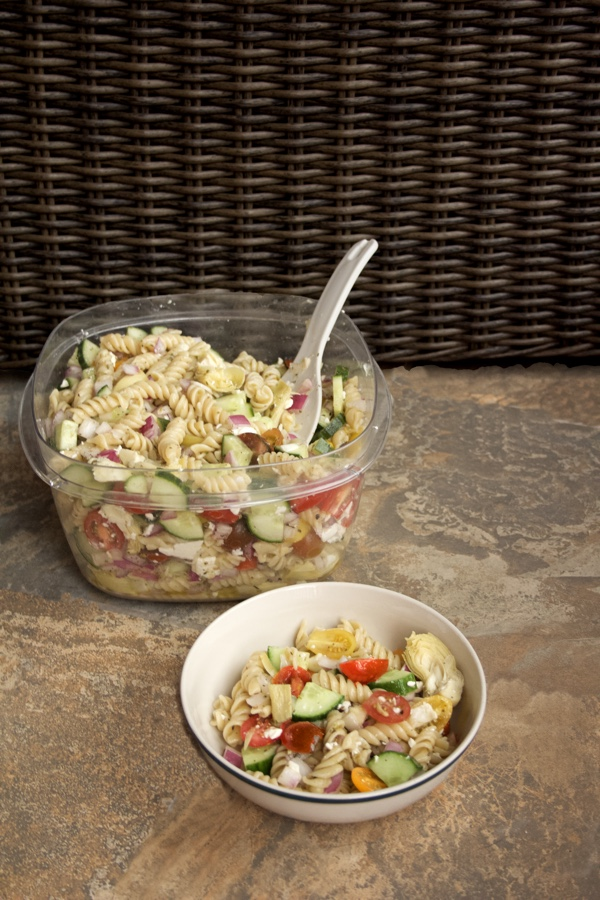 Easy Greek Pasta Salad in an individual bowl that is sitting in front of a tub of the salad.