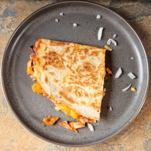 Top-down view of BBQ Chicken Quesadillas on a gray plate with a sprinkling of onions.