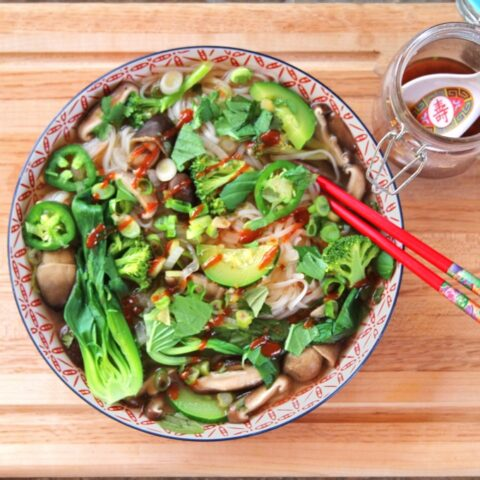 Overhead view of a bowl of Instant Pot Vegetable Pho Soup, loaded up with herbs and garnishes, with a red pair of chopsticks. The bowl sits next to a jar of vegan nuoc cham.