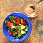An individual serving of Meal-Prep House Salad & Homemade Thousand Island Dressing in a blue bowl. The salad is piled with tomatoes, sliced cucumbers, scallions, and grated carrots. The dressing is on the side in a clear ramekin.
