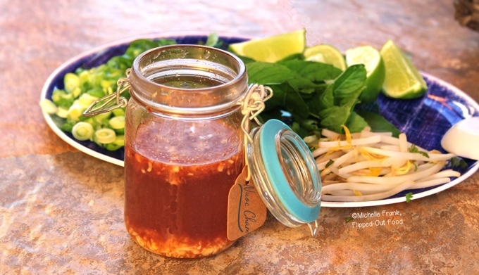 Quick Nuoc Cham Sauce: a side view of a mason jar full of sauce sitting in front of a platter of herbs, lime wedges, and sliced scallions and jalapenos.
