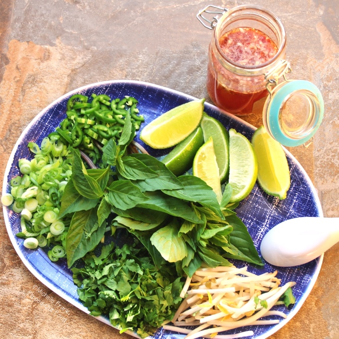Top view of a jar of Quick Nuoc Cham Sauce sitting next to a blue platter loaded with condiments for pho, including sliced scallions and jalapenos, lime wedges, mung bean sprouts, Thai basil, and chopped cilantro.