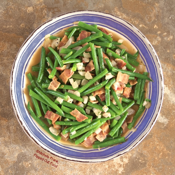 Overhead view of Green Beans with Bacon and Onions in a blue-rimmed bowl.