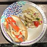 Grilled Italian Sausage Sandwiches with Pepper-Onion Foil Packs on a decorative paper plate with Greek Pasta Salad. The plate is sitting on a rustic picnic table located at Devil's Lake State Park in Wisconsin.
