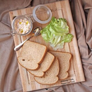 Tangy Deviled Ham & Cheese Spread in a small jar sits on a cutting board along with slices of wheat bread and lettuce.
