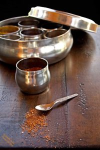 5-Ingredient Homemade Taco Seasoning scattered on a tabletop in front of a tiny spoon. Behind sits a metal cup and an Indian spice box.