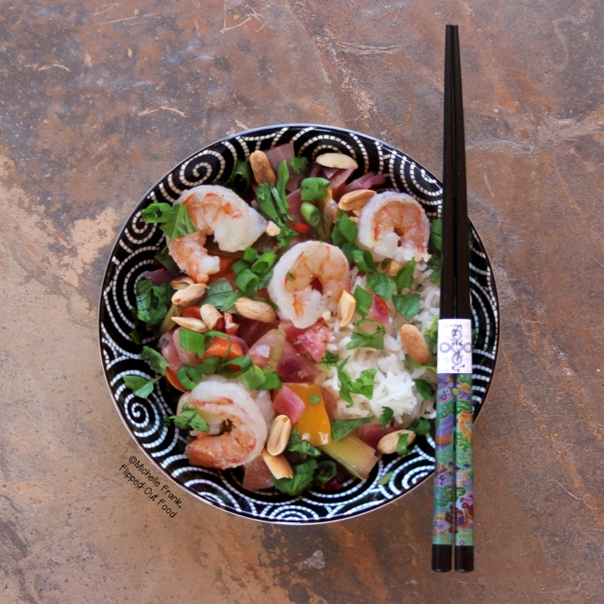 Top view of a black bowl with white swirls, filled with Shrimp Thai Basil Stir-Fry. Dig in with the ornate chopsticks sitting on top of the bowl.