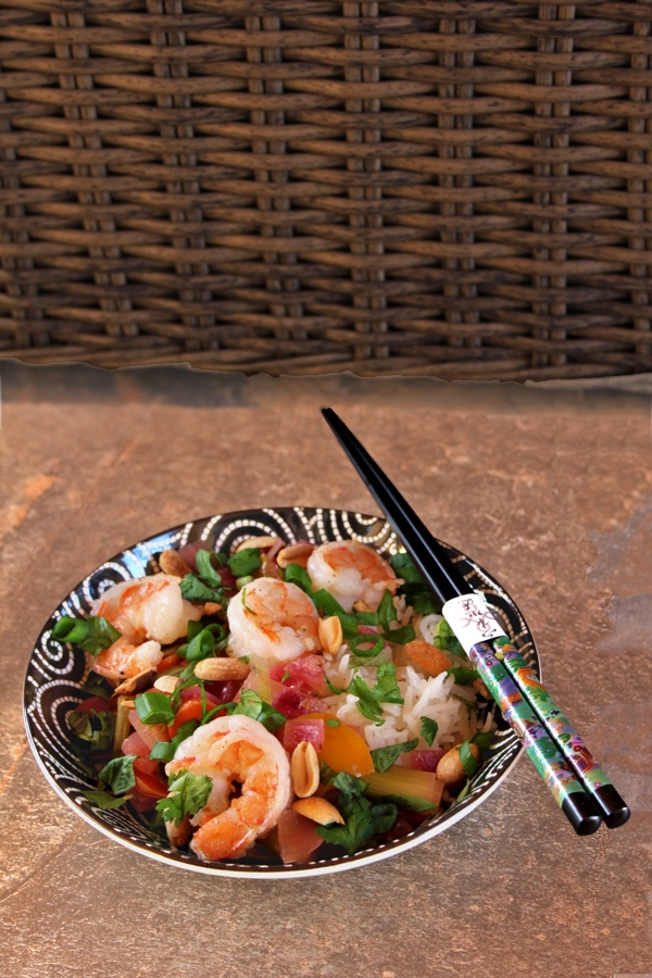Shrimp Thai Basil Stir-Fry: a side view of a black bowl with white swirls filled with the stir-fry. The bowl sits in front of a brown wicker background and has a set of ornate chopsticks on top.