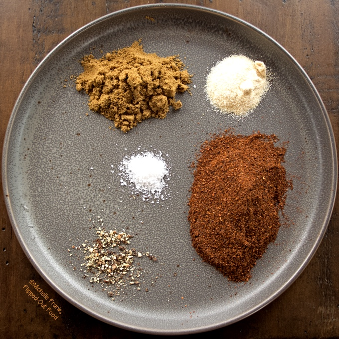 The separate spices for 5-Ingredient Homemade Taco Seasoning are shown in their relative ratios on a gray plate. These include 5 tbsp ancho chile powder, 3 tbsp ground cumin, 2 tsp granulated onion powder, 1 tsp salt, and 1 tsp freshly ground black pepper.
