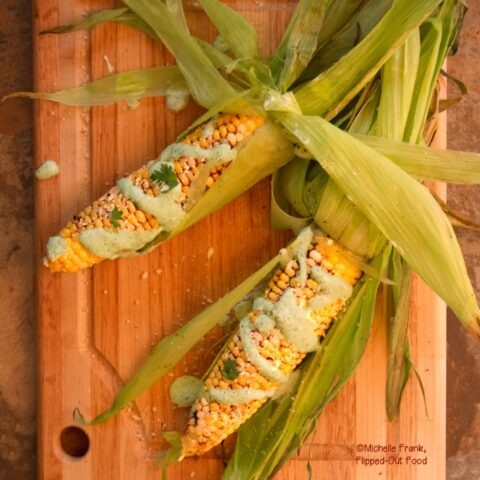 Elote: Mexican Street Corn with Jalapeno-Cilantro Crema. 2 ears sit on a wooden cutting board, with husks flying, drizzled with crema and sprinkled with cilantro.