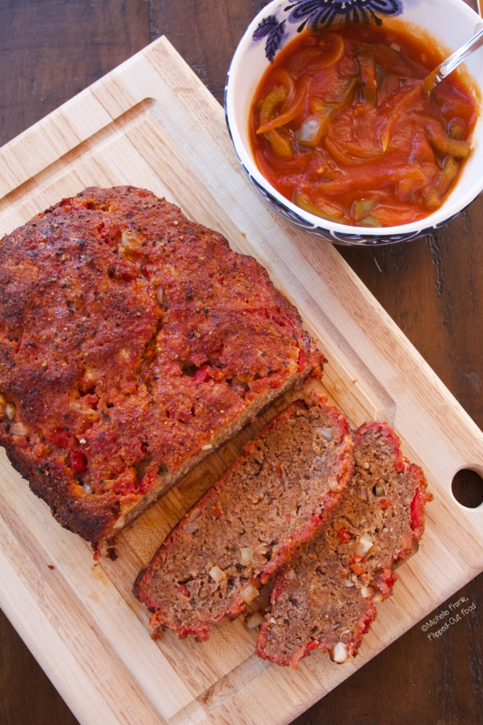 Mediterranean-Style Meatloaf on a wooden cutting board next to a bowl with tangy pepper-tomato sauce.