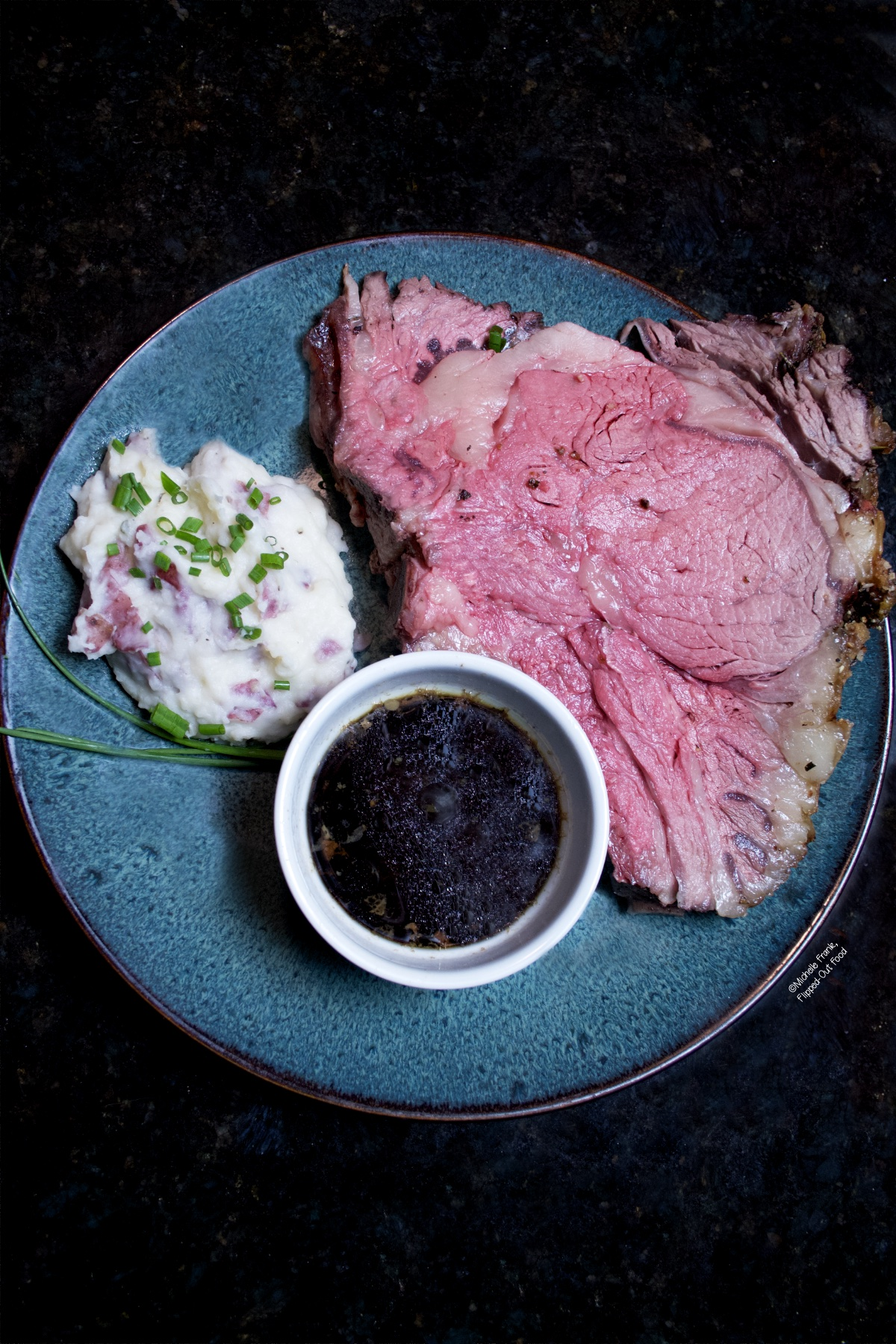 Date Night Prime Rib Roast with simple au jus. A giant slab of prime rib is served on a blue ceramic plate next to a white ramekin of au jus and a serving of skin-on mashed potatoes with horseradish.