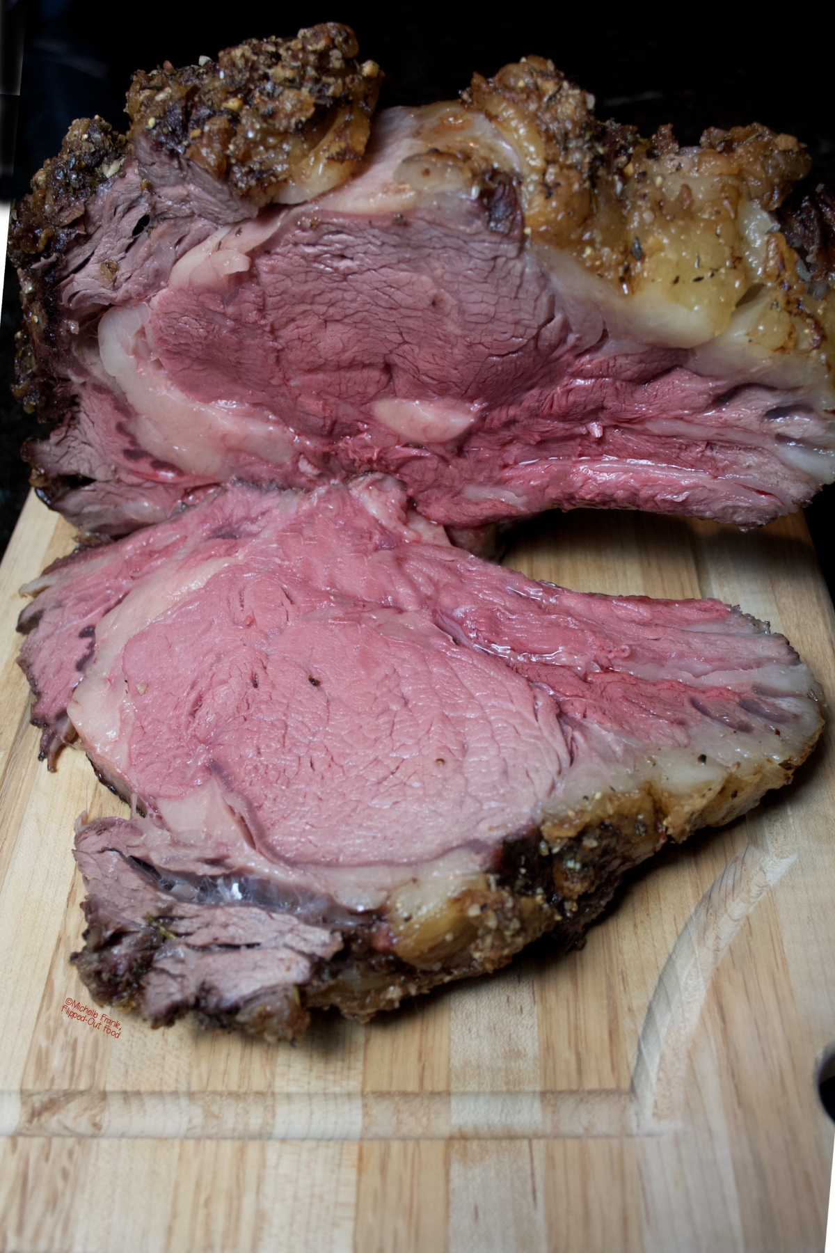 Date Night Prime Rib Roast on a wooden cutting board, with a single slab sliced off and laying on the board.