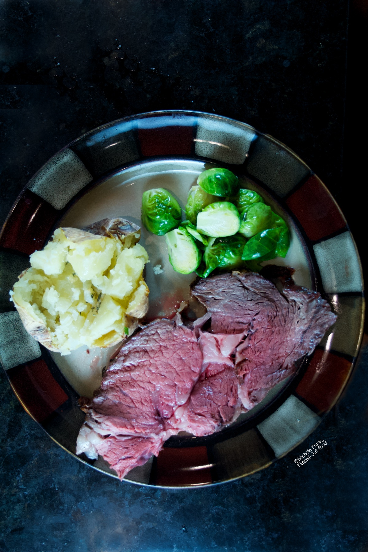 Date Night Prime for Two: a slab of prime rib on a ceramic plate with a baked potato and steamed Brussels sprouts.
