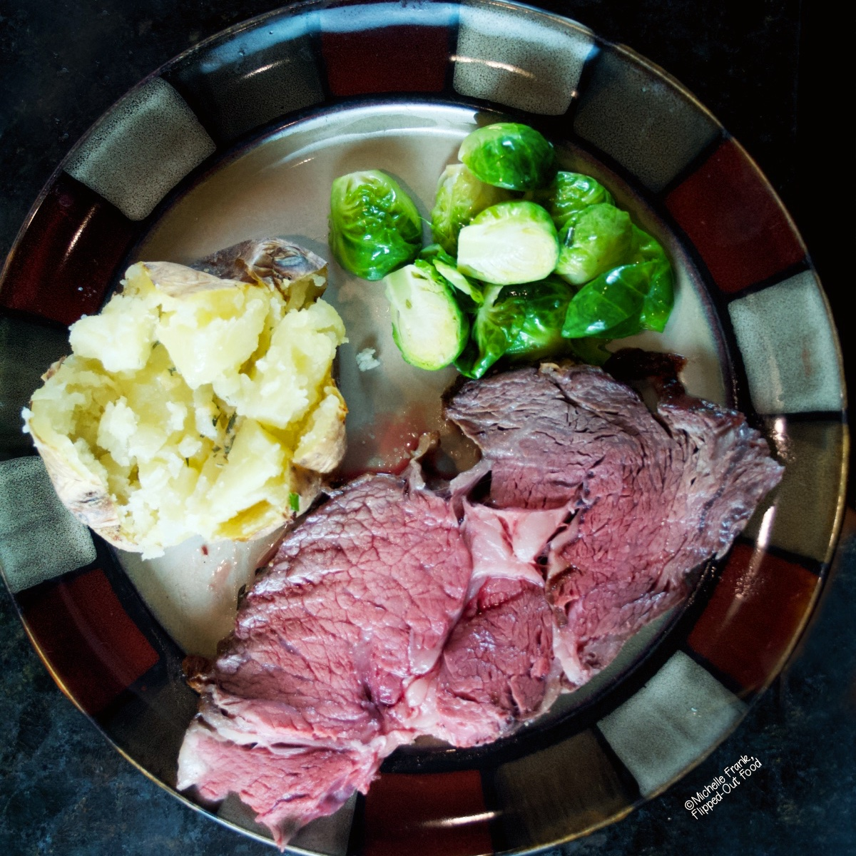 Date Night Prime Rib Roast, showing a single slice on a plate with a baked potato and Brussels Sprouts