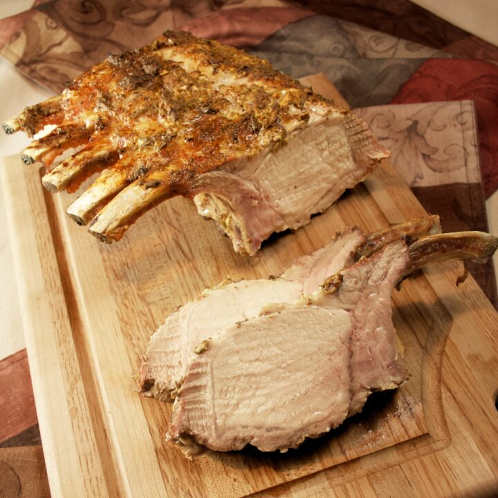 Herb-Roasted Rack of Pork on a cutting board with two gigantic chops sliced off.