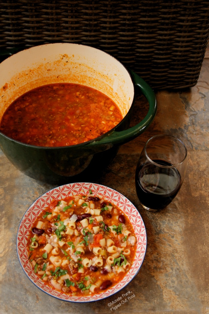 A serving of Easy Pasta e Fagioli Soup in a red and white bowl with the pot full of soup in the background, and a glass of red wine sitting nearby.