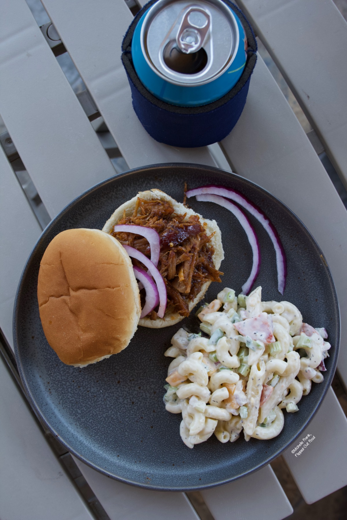Overhead image of a serving of pasta salad with a pulled pork sandwich on a gray plate.