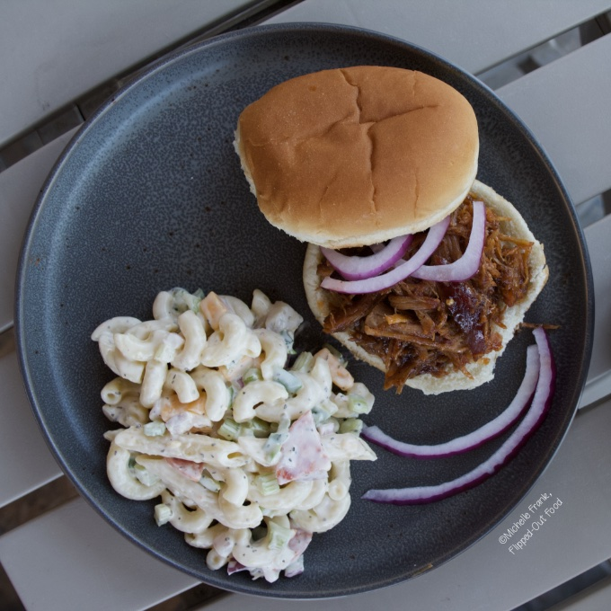 Creamy Pasta Salad: a serving on a grey plate next to a pulled pork sandwich and sliced red onion.