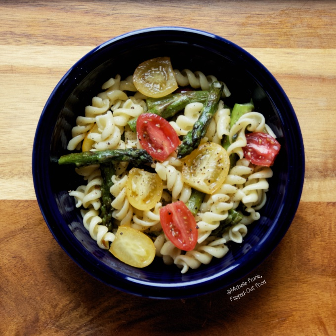 Springtime Tomato Asparagus Pasta serving in a blue bowl.