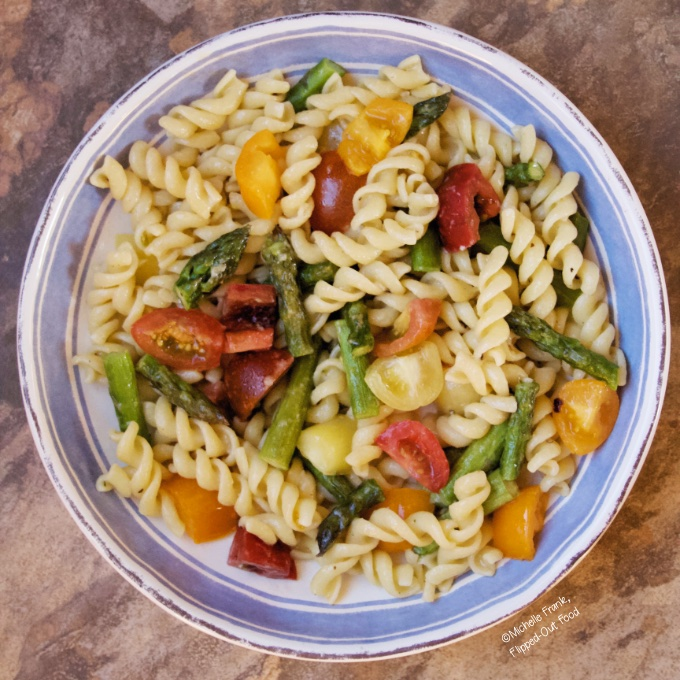 Springtime Tomato Asparagus Pasta serving in a blue and white bowl.