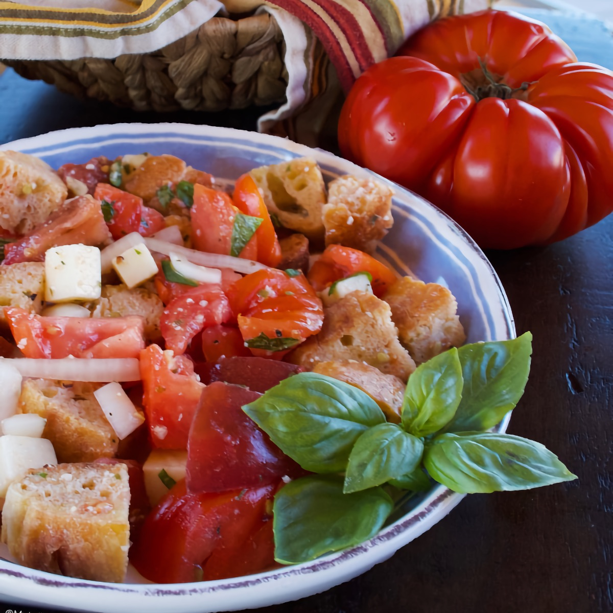Summer Panzanella Salad garnished with a sprig of basil. An heirloom tomato sits in the background.