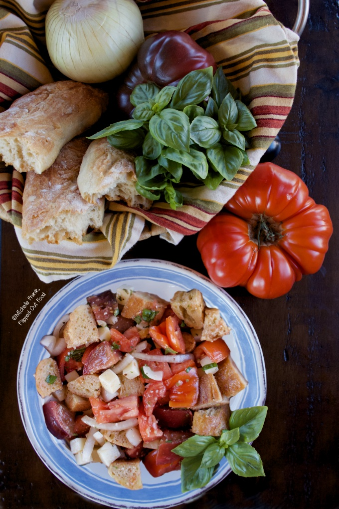 Summer Panzanella Salad serving in a blue and white bowl garnished with a sprig of basil. The bowl sits in front of a bursting-ripe, red heirloom tomato and a basket with torn baguette, basil, onion and a purple heirloom tomato.
