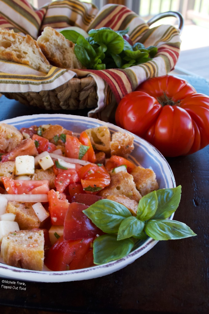 Favorite recipes for July 4th: Summer Panzanella Salad in a blue and white bowl, garnished with a sprig of basil. The bowl sits in front of an heirloom tomato and a bread basket with torn baguette.