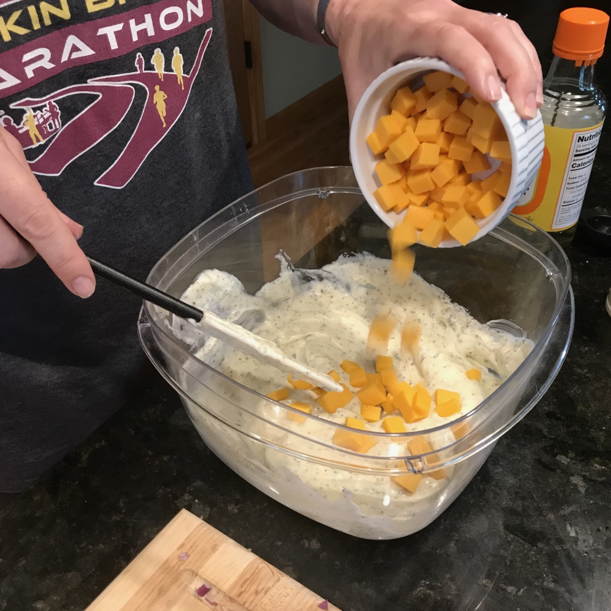 Adding cubed cheese to the pasta salad dressing and mixing to coat thoroughly.