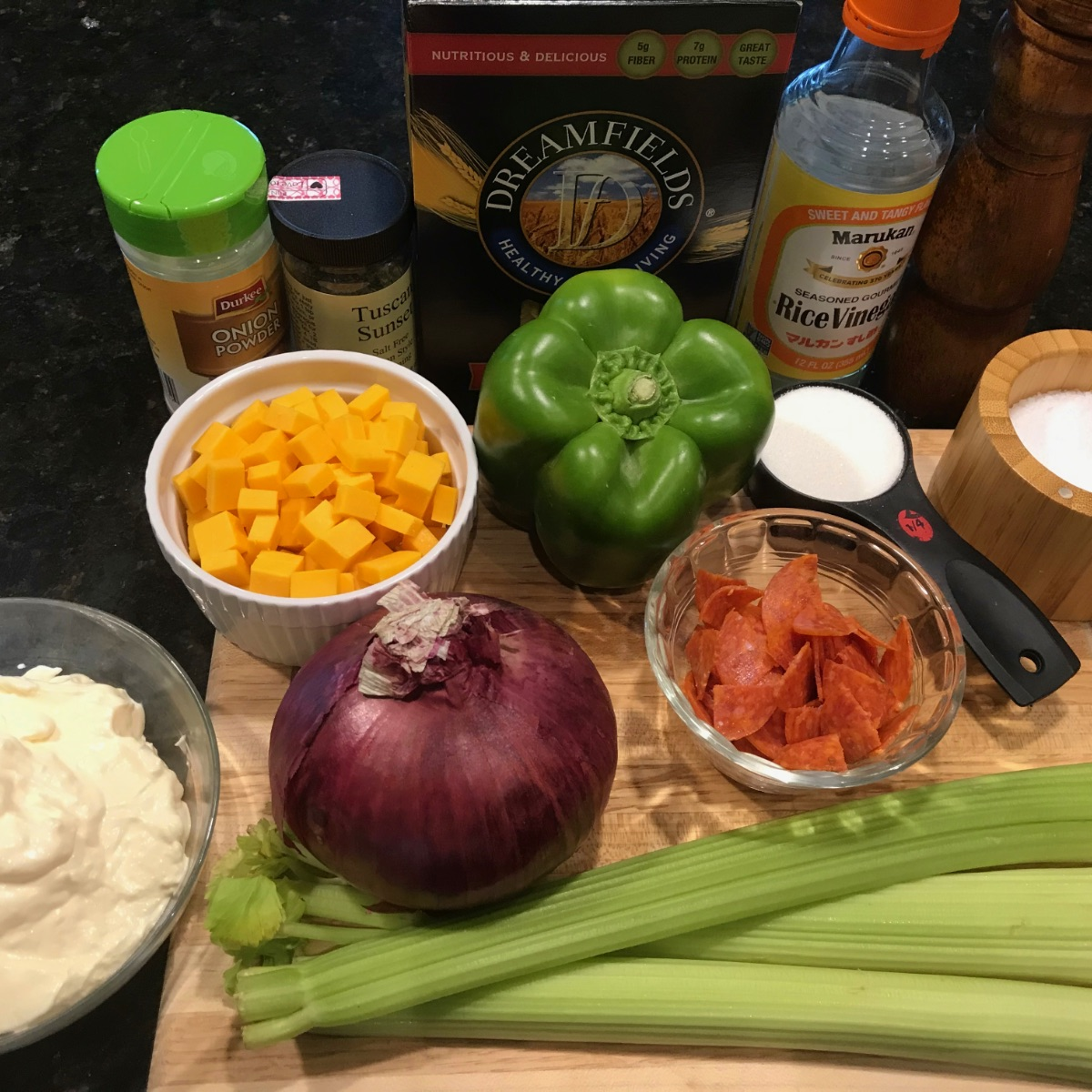 image of Ingredients for this pasta salad (clockwise from top left): onion powder, Italian herb mix, pasta, rice vinegar, salt, sugar, pepperoni, green bell pepper, red onion, cubed cheddar cheese, and mayonnaise.