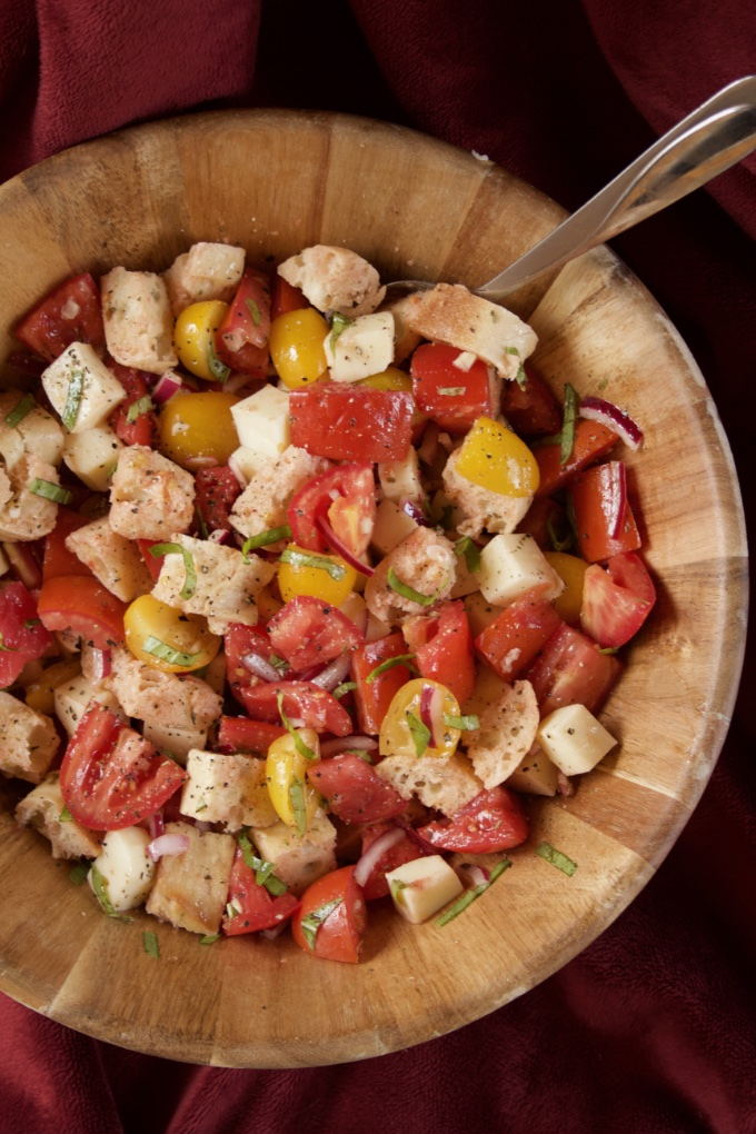 Close-up of Summer Panzanella Salad in a wooden salad bowl with a serving spoon.