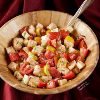 Side-view of Summer Panzanella Salad in a wooden serving bowl with a serving spoon.