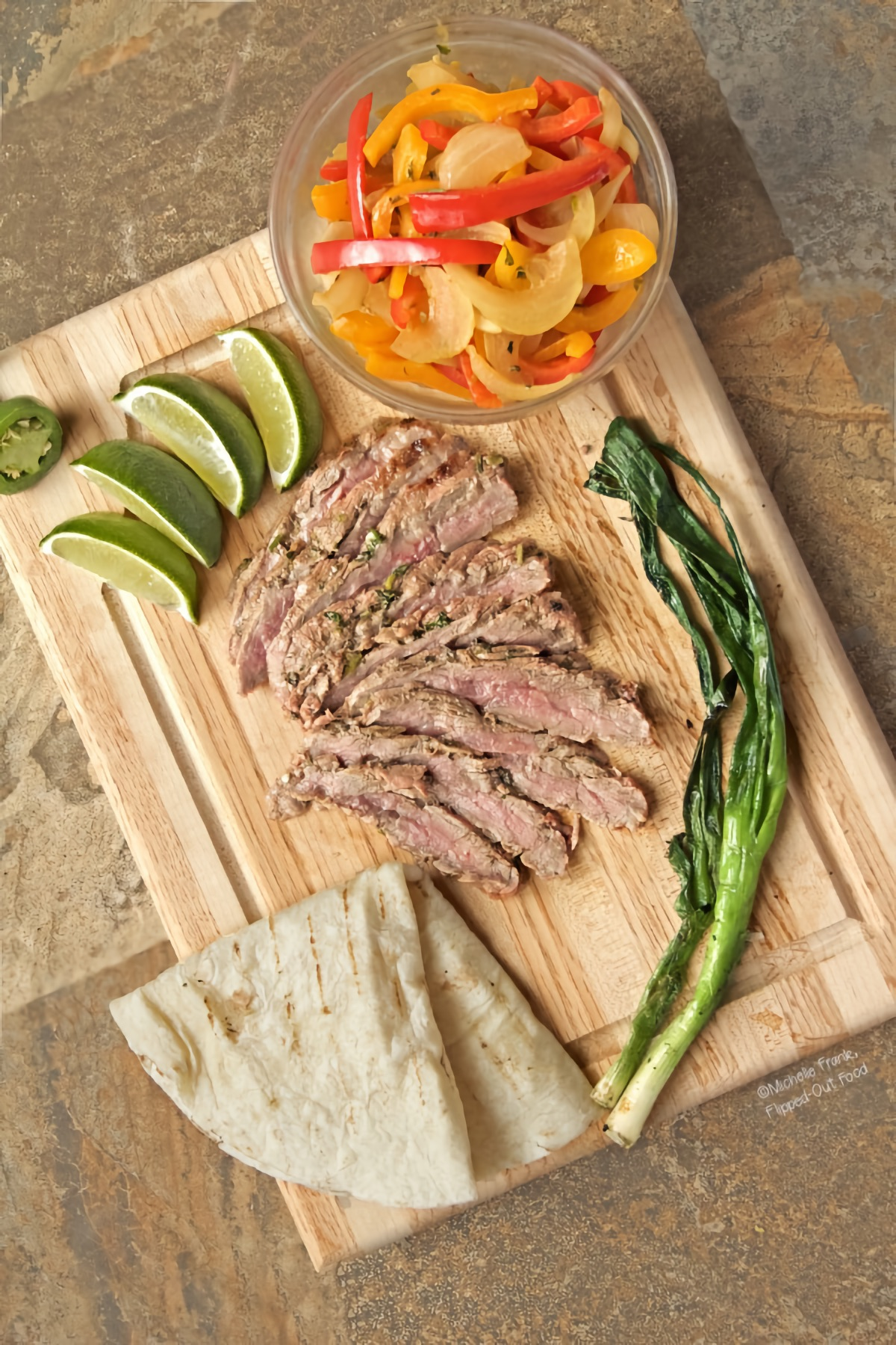 Top view of carne asada with fajita vegetables arranged on a cutting board with a folded flour tortilla, grilled scallions, lime wedges, and the cut end of a jalapeno pepper.