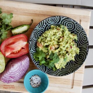 Easy Cutting-Board Guacamole in a black bowl set atop a wooden cutting board. Next to the bowl sits a ramekin with salt and pepper, a cut red onion, squeezed lime, cut tomato, cut jalapeno, and a sprig of cilantro.
