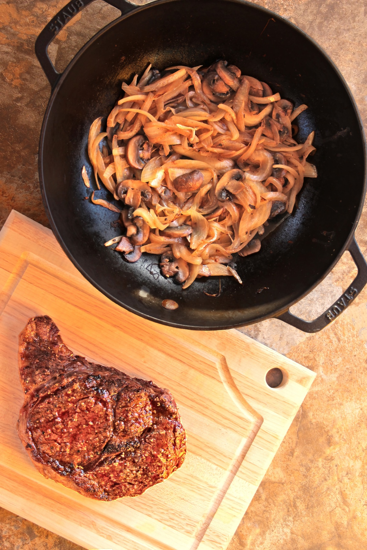 Grilled Ribeye Steak with Caramelized Mushrooms and Onions: the mushrooms and onions are finished in the skillet, which sits just behind a huge ribeye steak resting on a wooden cutting board.