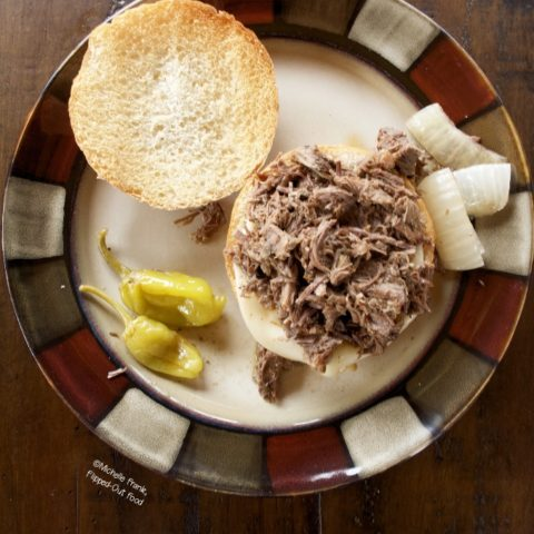 Instant Pot Mississippi Pot Roast Sandwiches: a single sandwich on a plate with onions and pepperoncini peppers. The top bun is set on the side.