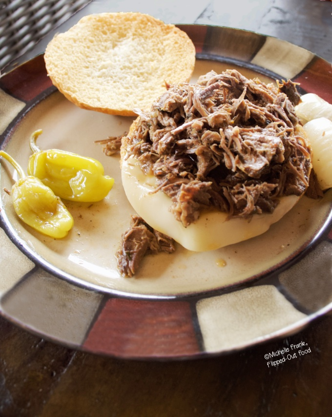 Instant Pot Mississippi Pot Roast Sandwiches: close-up side view of a single sandwich on a plate with onions and pepperoncini peppers.