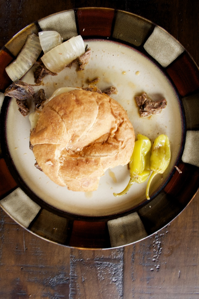 Instant Pot Mississippi Pot Roast Sandwiches: top view of a single sandwich on a plate with onions and pepperoncini peppers. A bite has been taken out of the sandwich.