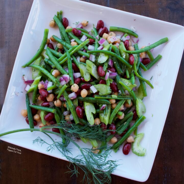 Tangy 3-Bean Salad on a white serving dish with a sprig of dill.