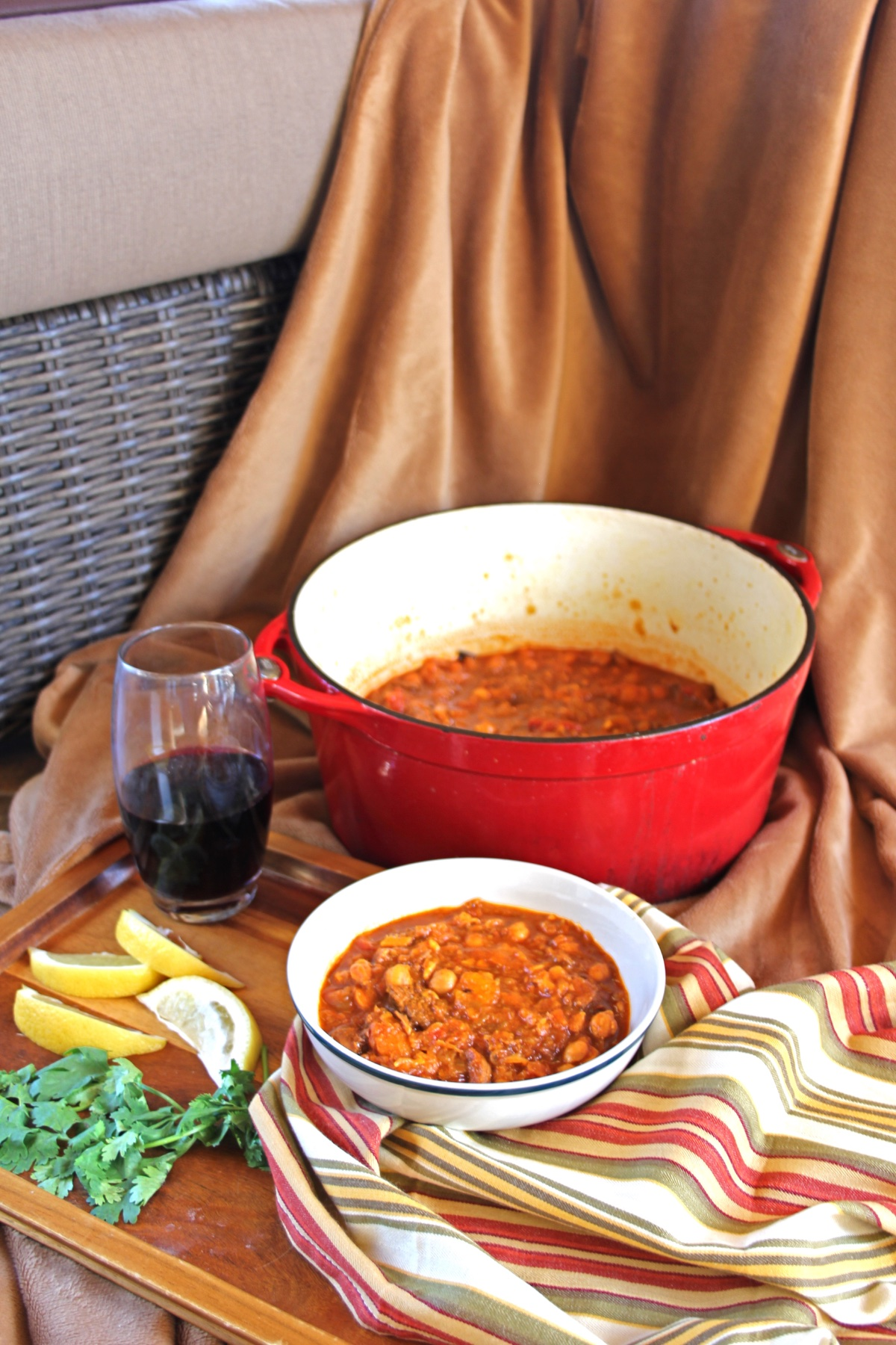 Easy Soups for Fall: Moroccan Lamb Stew. A bowl of stew sits in front of the stew pot, surrounded by lemon wedges and a glass of red wine.