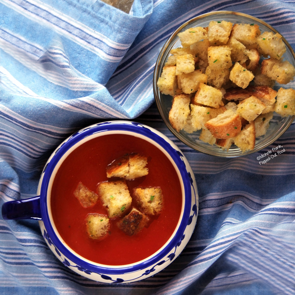 Easy Soups for Fall: A blue and white ceramic bowl of soup garnished with croutons, sitting on top of a blue and white striped cloth, next to a bowl of freshly toasted homemade croutons.
