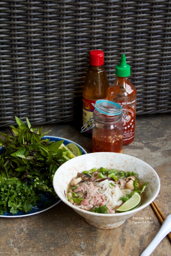 Real Deal Beef Pho Noodle Soup next to a platter of garnishes, nuoc cham, hoisin sauce, and sriracha.