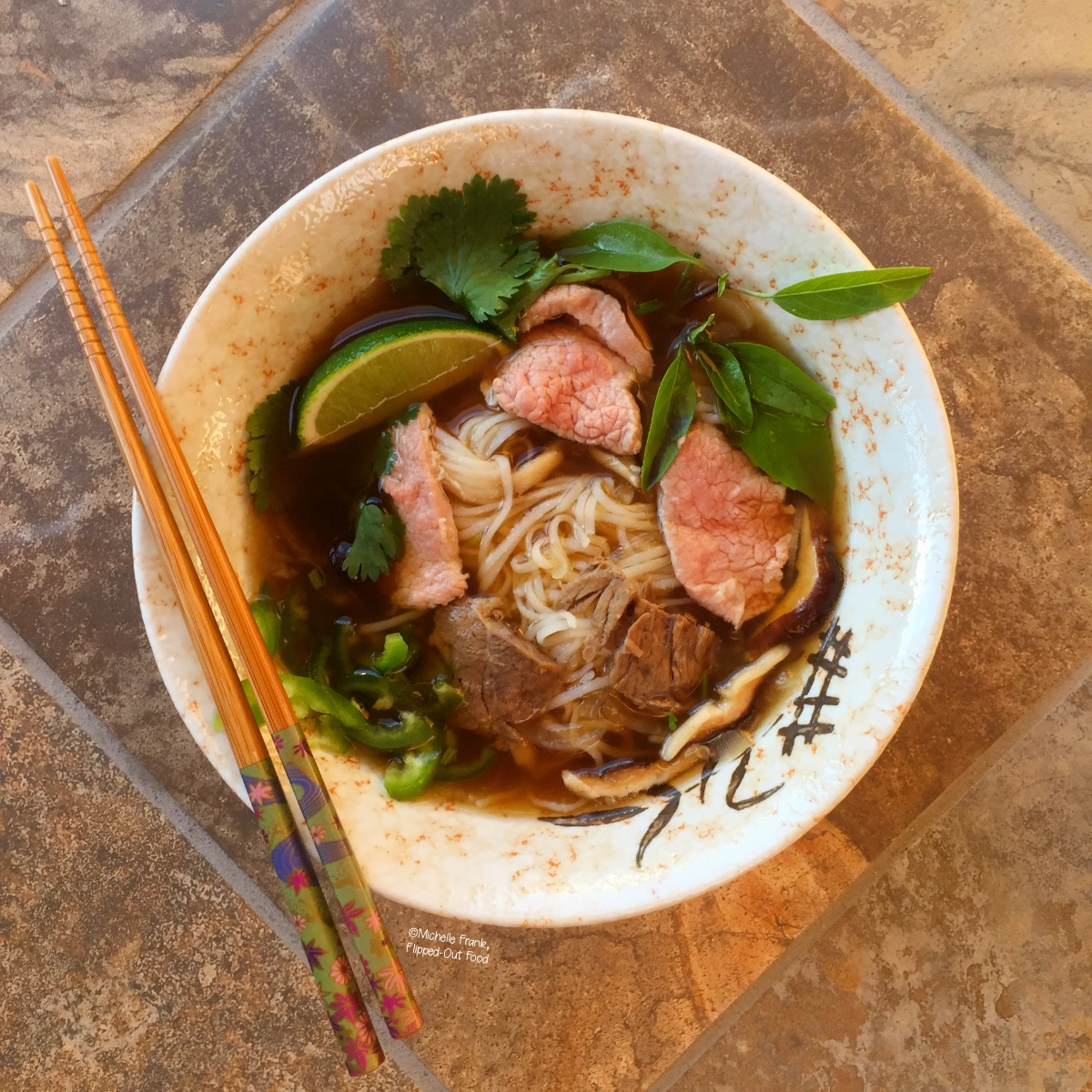A bowl of Real Deal Beef Pho Noodle Soup, garnished with herbs and a lime wedge. A pair of chopsticks sits on top of the bowl.