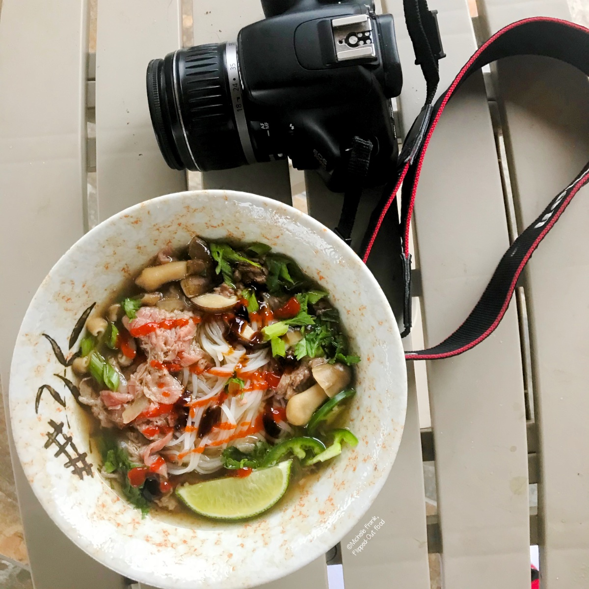 A bowl of Real Deal Beef Pho Noodle Soup sitting next to a camera.