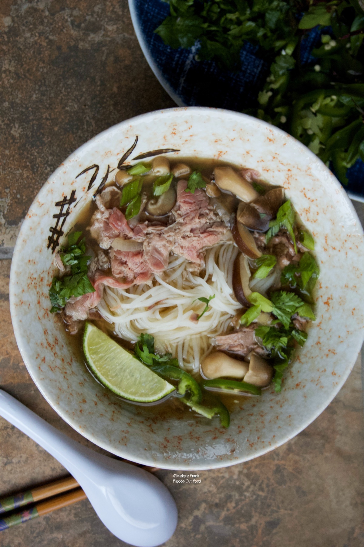 Real Deal Beef Pho Noodle Soup next to a soup spoon, chopsticks, and a platter of garnishes.