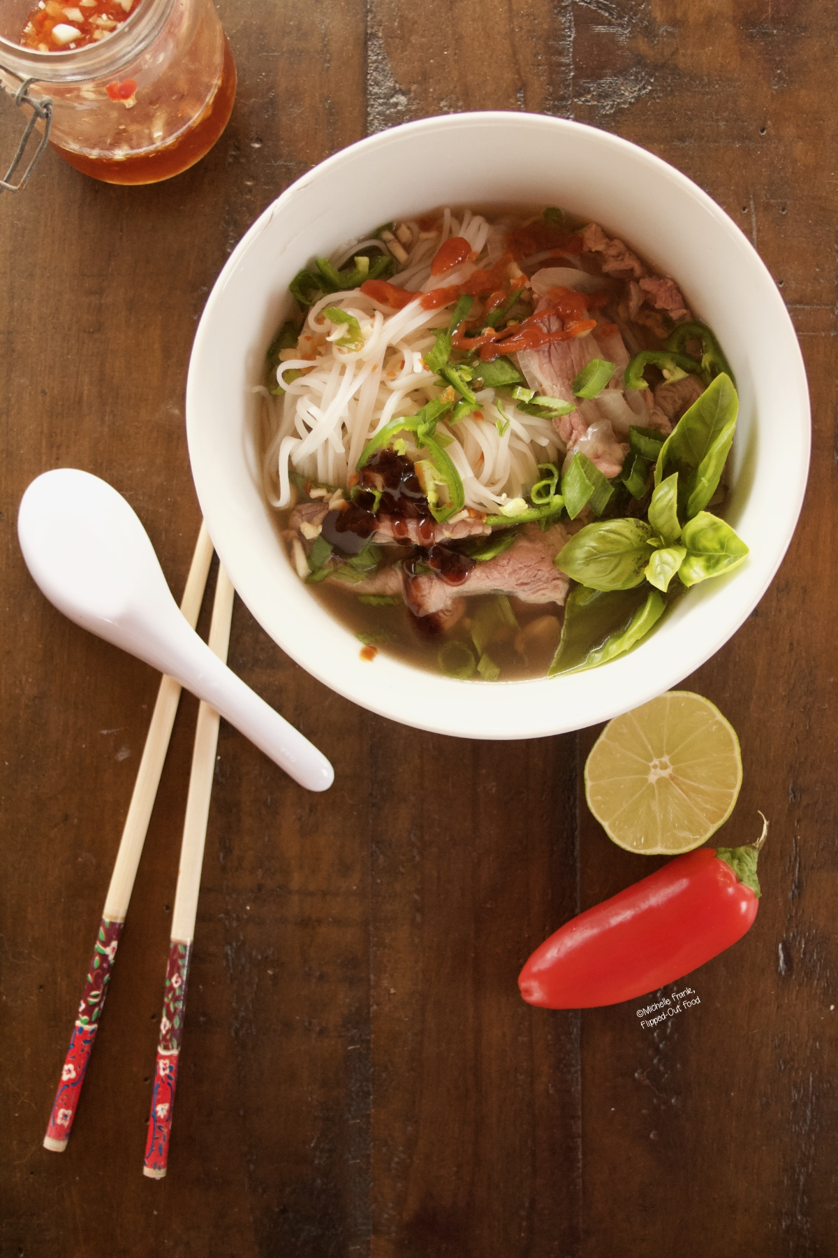 A bowl of Real Deal Beef Pho Noodle Soup sitting next to a jar of nuoc cham, chopsticks, spoon, half a lime, and a red chili.