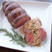 Roast Beef Tenderloin with Green Peppercorn Sauce, the roast on a white platter with two sliced medallions covered in sacue.