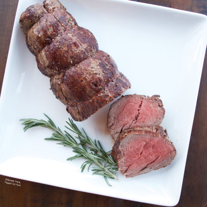 Roast Beef Tenderloin with Green Peppercorn Sauce on a serving platter with two slices cut. The platter is garnished with a sprig of rosemary.