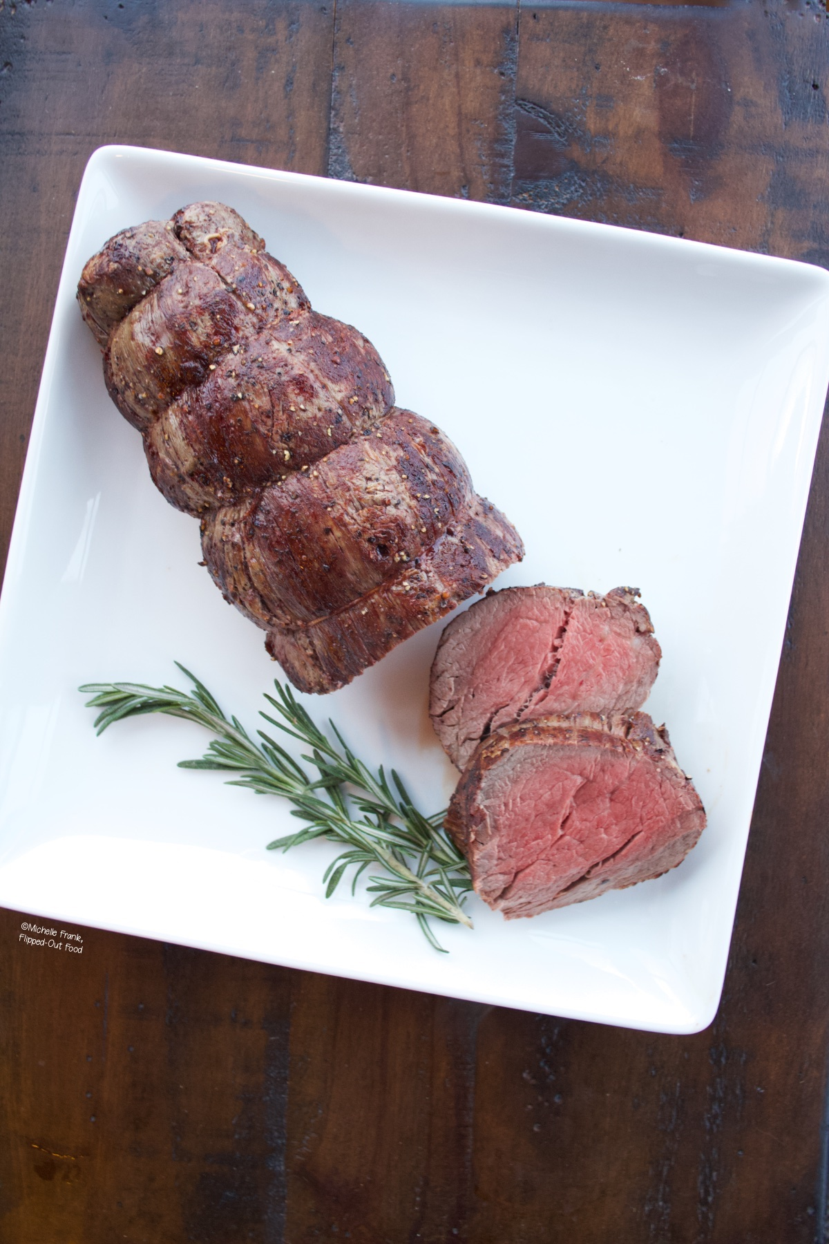 Roast Beef Tenderloin with Green Peppercorn Sauce on a serving platter with two slices cut. The platter is garnished with sprigs of rosemary.